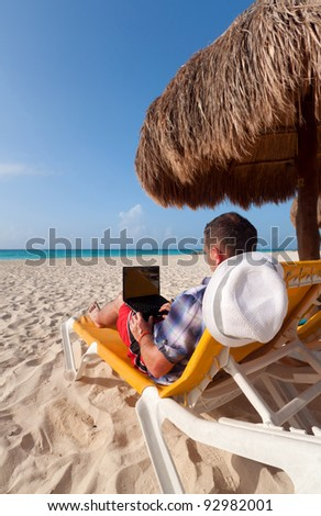 Man with laptop relaxing on the deckchair at the Caribbean sea