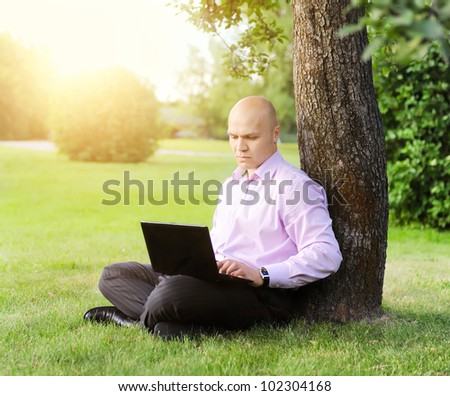man with laptop sitting near a tree in the park