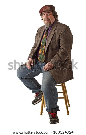 Man with large build sits on stool, dressed casually in tweed cap, jacket and jeans. He smiles and  sits forward with hands on knees. Vertical, isolated on white background, copy space. - stock photo
