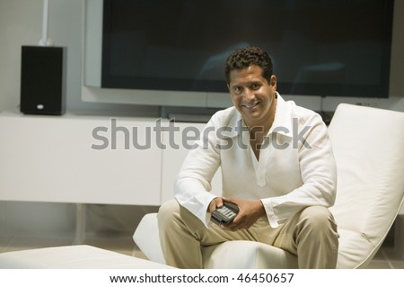 Man with Large Screen TV and Remote Control - stock photo