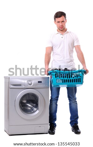 man with laundry basket posing next to a washing machine isolated on white background