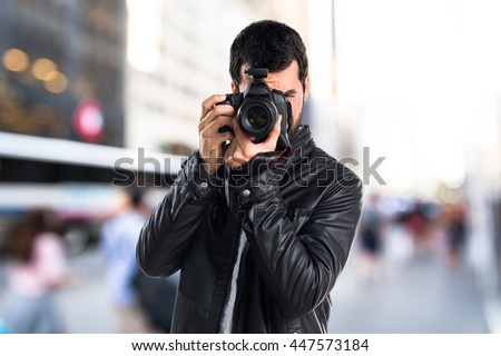 Man with leather jacket photographing on unfocused background