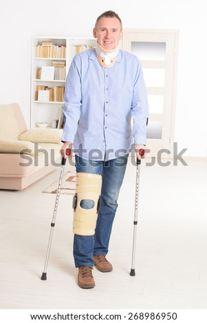 Man with leg in neck brace, knee cages and crutches for stabilization and support  - stock photo