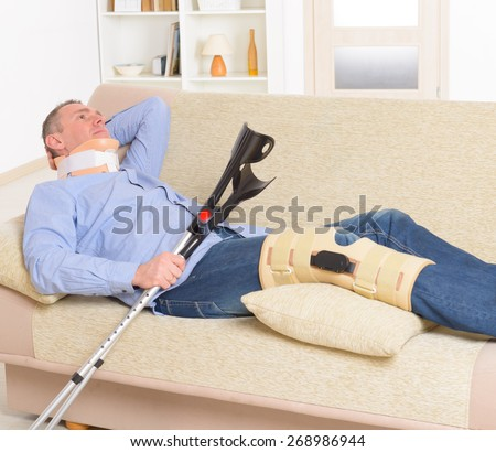 Man with leg in neck brace, knee cages and crutches for stabilization and support resting on a sofa - stock photo