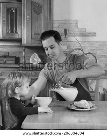 man with little boy in the kitchen preparing a meal. retro - stock photo