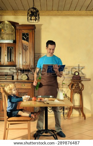 man with little boy in the kitchen preparing a meal. retro