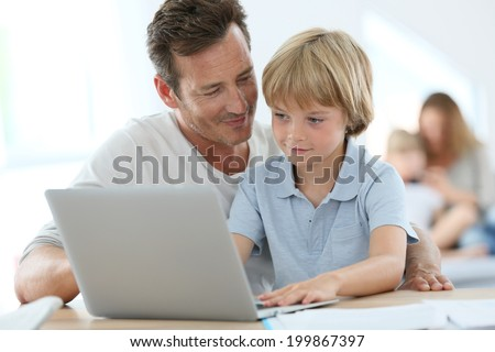 Man with little boy playing on laptop computer