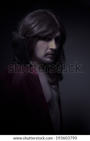 man with long hair and black coat - stock photo