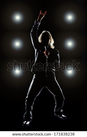 Man with long hair holding a microphone, against a black background with lights behind him.  - stock photo