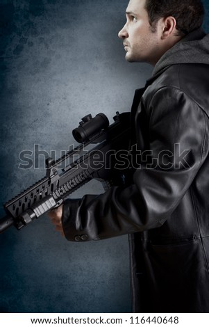 Man with long leather jacket and assault rifle - stock photo