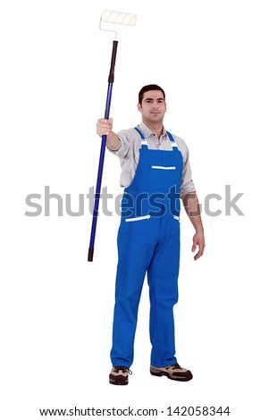 Man with long paint roller - stock photo
