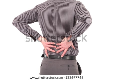 Man with lower back pain or backache caused by injury, stress or bad posture holding his back with both his hands, cropped torso portrait on white - stock photo
