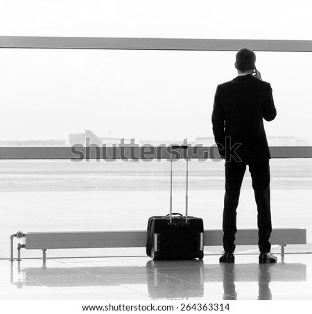 Man with luggage in the airport. Black and white. - stock photo
