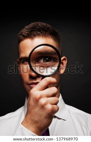 Man with magnifier on dark background