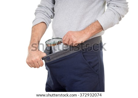 Man with magnifying glass looking into his tracksuit pants - stock photo