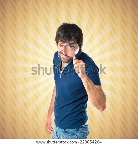 Man with magnifying glass over pop background - stock photo