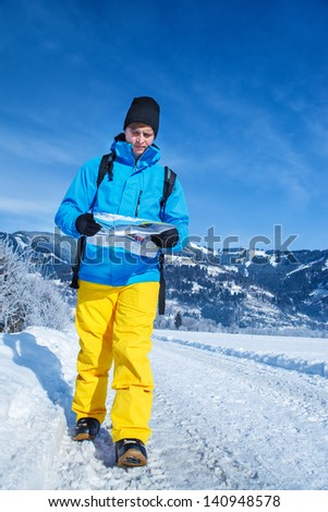 Man with map walking through snowy fields in the Alps