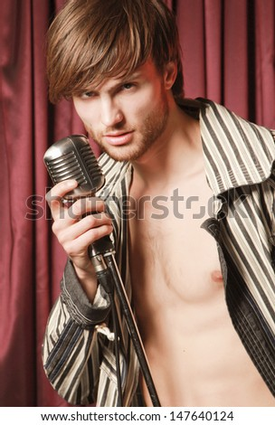 man with microphone on the stage - stock photo