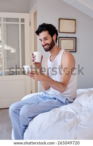 man with mobile cellphone and coffee sitting on bed at home - stock photo