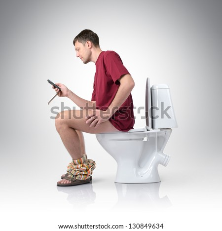 Man with mobile phone sitting on the toilet - stock photo