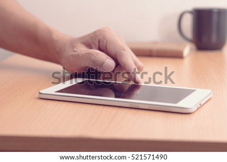 Man with modern mobile phone in hands touching on a blank screen.