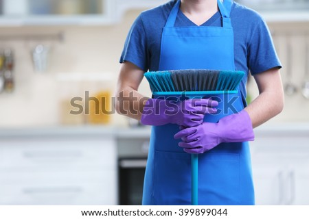Man with mop in the kitchen - stock photo