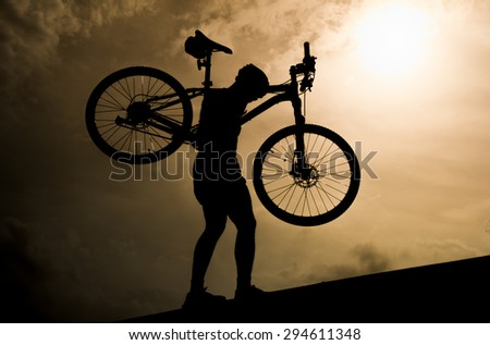 Man with mountain bicycle lifted above him  in the evening - stock photo