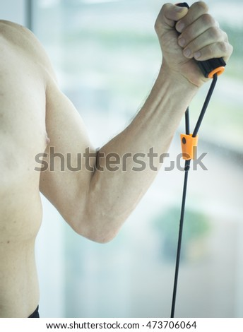 Man with muscular fit torso and attractive body in 40's exercising with resistance exercise bands with naked torso physique.
