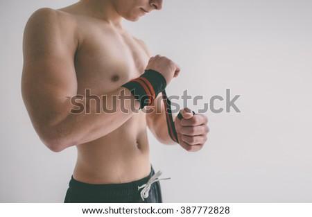 Man with muscular torso.  Closeup of a muscular young man lifting weights - stock photo