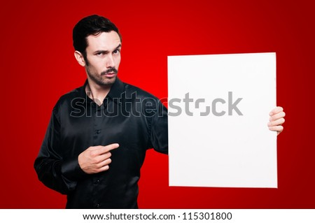 man with mustache and black jacket holding blank white board on red background