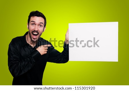 man with mustache and black jacket holding blank white board on yellow background
