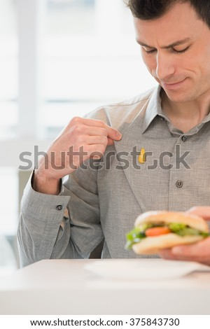 Man with mustard on his shirt - stock photo