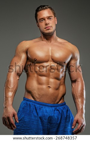 Man with naked musculartorso posing in studio