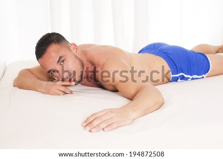 man with naked torso lying in bed