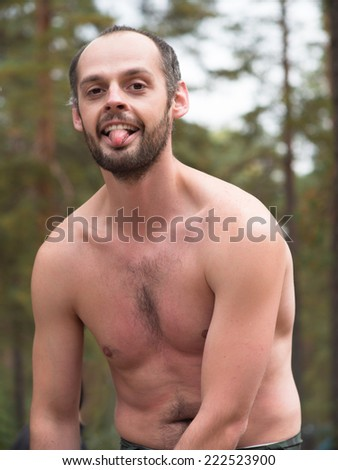 Man with naked torso showing tongue on blurred background - stock photo