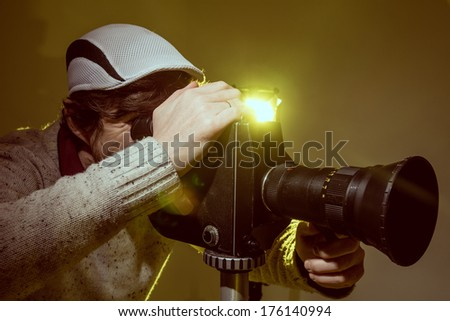 Man with old film movie camera. Shooting of the film, advertising and music video - stock photo