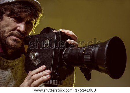 Man with old film movie camera. Shooting of the film, advertising and music video