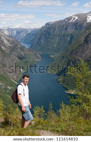 Man with on the background the Naeroyfjord - famous UNESCO World Heritage Site in Norway. - stock photo
