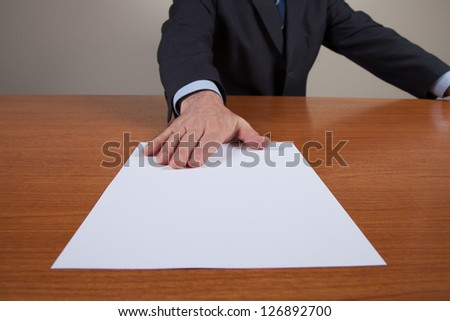 Man with one white sheet put on the table. He is in the meeting room and he is reached out forward his hand with the sheet.