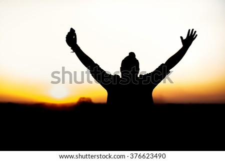 Man with open arms in front of a sunset.