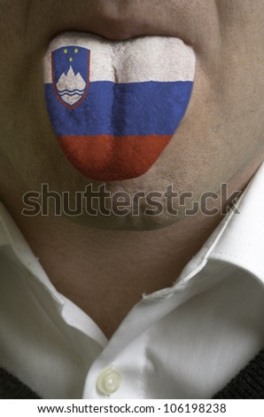 man with open mouth spreading tongue colored in slovenia flag as symbol of values like teaching, learning, multilingual speaking of different languages - stock photo