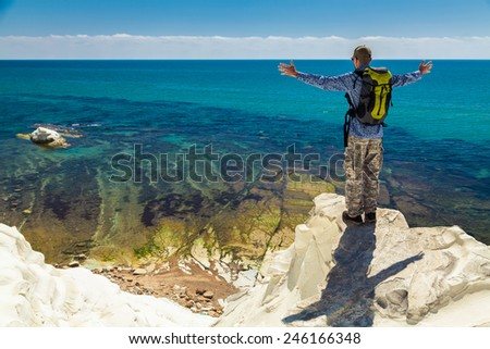 man with opened arms standing on the edge of a cliff, enjoying amazing sea view - stock photo
