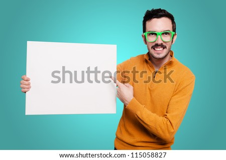 man with orange sweater and green glasses holding blank white board on blue background