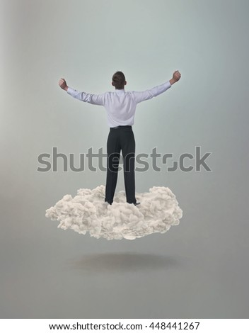Man with outstretched arms floating on a cloud