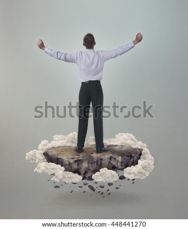 Man with outstretched arms floating on a rock surrounded by clouds