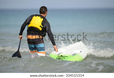 man with paddleboard and paddle heading out into the ocean wearing a yellow life jacket - stock photo