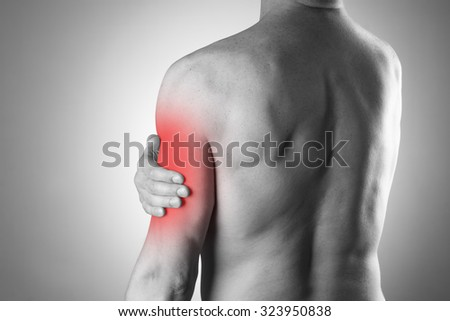 Man with pain in shoulder. Pain in the human body. Black and white photo with red dot - stock photo