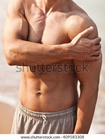 Man with pain in shoulder. Pain in the human body on a sea background. - stock photo