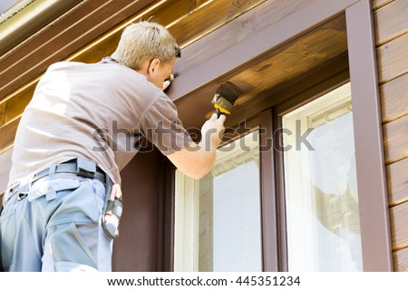 man with paintbrush painting wooden house exterior - stock photo