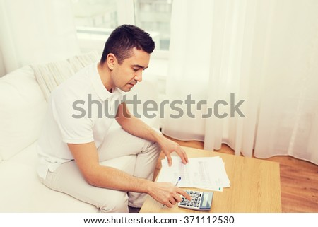man with papers and calculator at home - stock photo